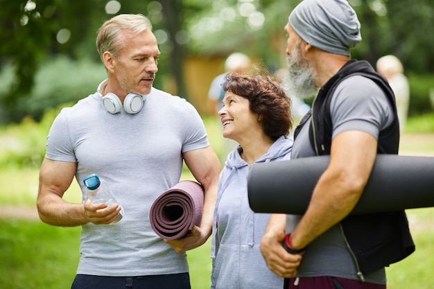 Two sporty mature men and woman standing together in park discussing something before doing exercise