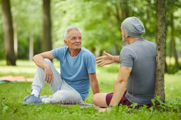 Два спортивных старших друга-мужчины сидят вместе на зеленой траве в парке и говорят о чем-то, снимок в полный рост
