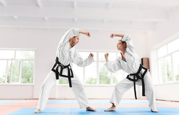 Two sporty woman fighting at karate training in martial arts school.
