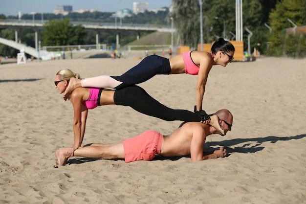 2人のスポーティな女性とハンサムな筋肉質の男性が女の子の上に二重板をやっています