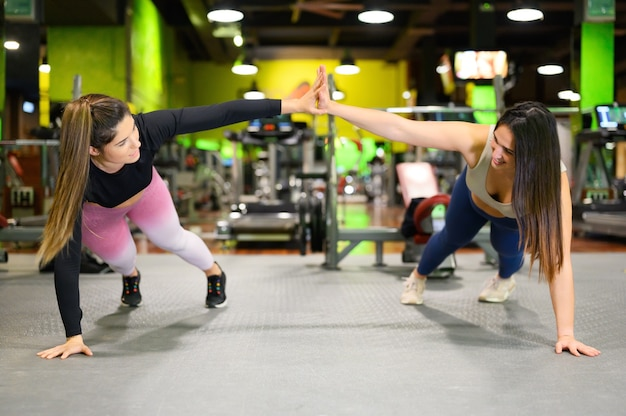 トレーニング中にハイタッチをしている2人のスポーティな女性がジムで腕立て伏せをしています。