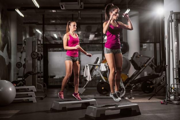 2つのスポーティな女性のフィットネス運動。