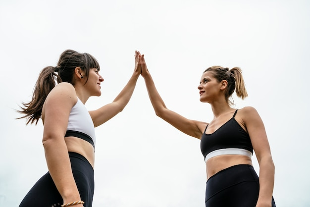 흰색 배경에 대해 스포츠 세션 후 서로 high-fiving 두 스포티 한 여성