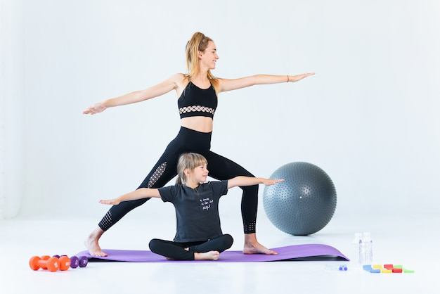 Two sporty women practice yoga in warrior pose in light gym against window