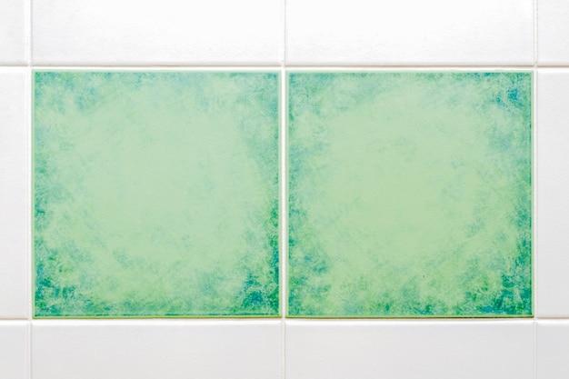 주위에 흰색 타일이있는 두 개의 사각형 녹색 타일