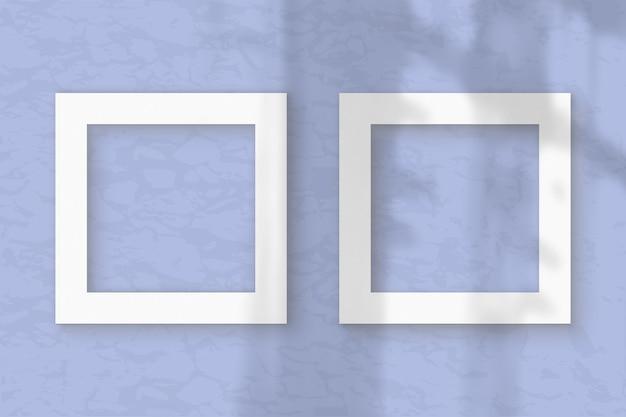 Два квадратных листа белой текстурированной бумаги на синем фоне стены. мокап с наложением теней растений. естественный свет отбрасывает тени из окна. плоская планировка, вид сверху. горизонтальная ориентация