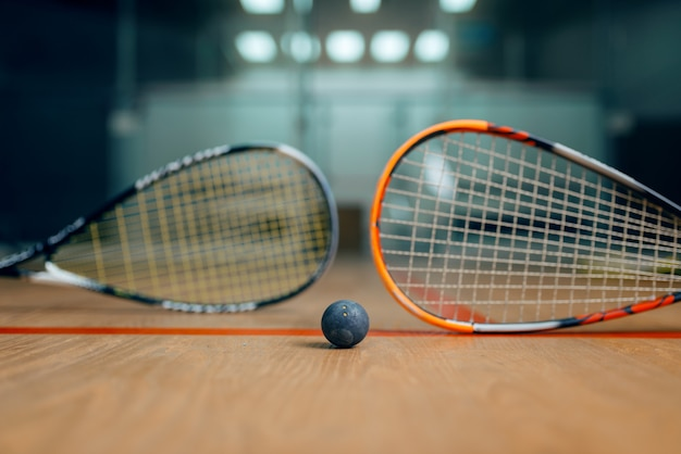 Two squash rackets and ball on court floor, nobody, game concept. active sport hobby, fitness workout for healthy lifestyle