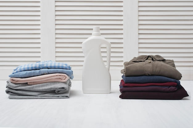 Two stack of folded clothes and detergent bottle