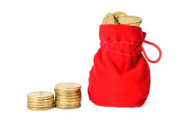 동전과 빨간 가방 두 스택 흰색으로 격리 동전으로 가득합니다. 현금 절약의 개념.