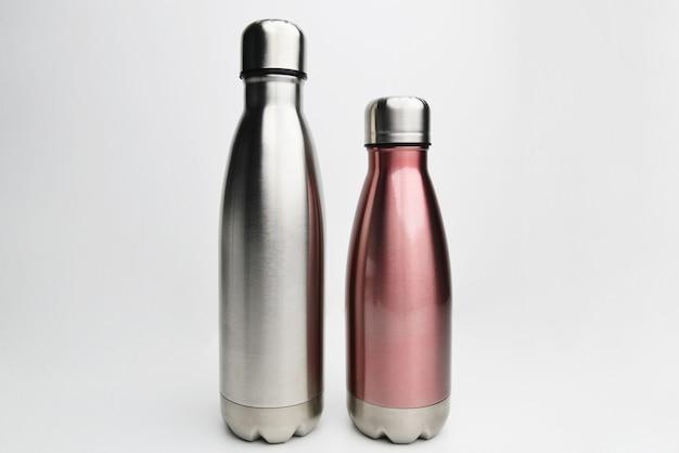 白い背景で隔離の2つのステンレス魔法瓶ウォーターボトルシルバーカラー空白のステンレス鋼の二重壁のトレーニングボトル白い背景で隔離のステンレス魔法瓶のクローズアップ