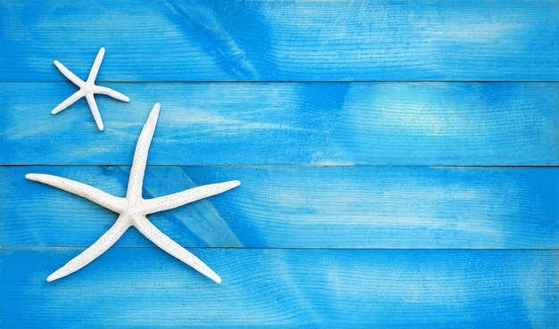 Two starfish on blue wooden . top view