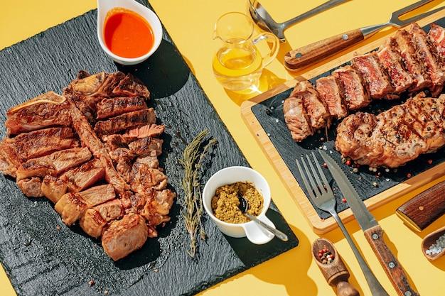Два стейка, стриплойн и т-бон, средней прожарки, на каменном фоне. концепция ужина на двоих