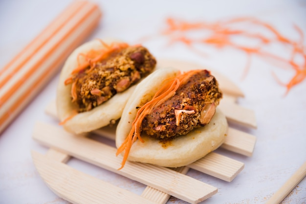 Two steamed buns on wooden tray over textured backdrop