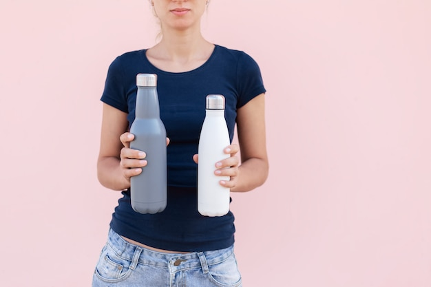 Two steel reusable, eco thermo water bottles in female hands. background of pastel pink color. be plastic free. zero waste.