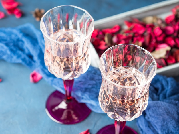 Two stemmed champagne glasses on blue textured background with pink dried flowers.