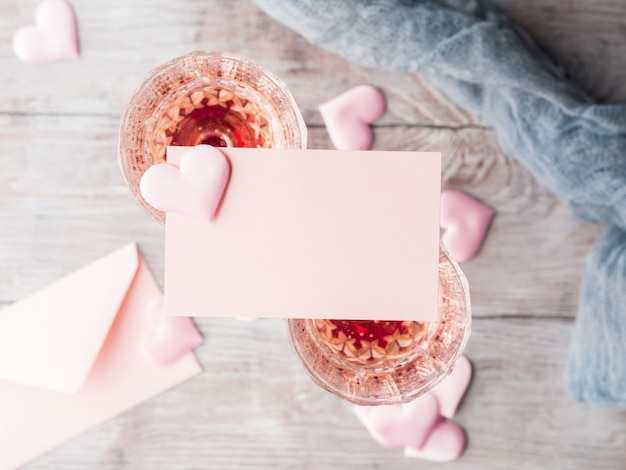 Two stemmed champagne glasses with pink hearts blank paper note card to fill with your text on wooden textured background.
