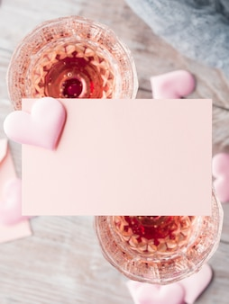 Two stemmed champagne glasses with pink hearts blank paper note card to fill with your text on wooden textured.