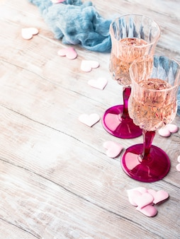 Two stemmed champagne glasses with pink hearts on wooden textured background.