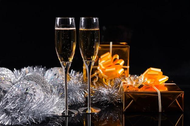 シャンパンでいっぱいの2つの茎のグラス、クリスマスシルバーの見掛け倒し、黒のコピースペースのあるテーブルに金色の光沢のある紙で包まれた2つのギフトボックス