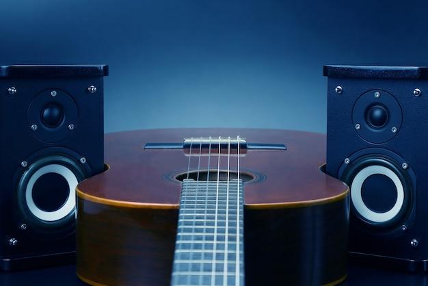 2つのステレオオーディオスピーカーとクラシックアコースティックギター