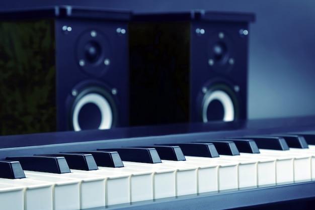 두 개의 스테레오 오디오 스피커와 피아노 건반이 어두운 배경에 닫혀 있습니다. 소리와 음악