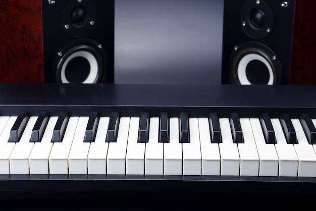 暗い背景に2つのステレオオーディオスピーカーとピアノの鍵盤のクローズアップ
