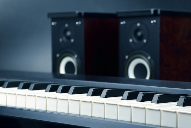 Two stereo audio speakers and piano keys closeup on dark