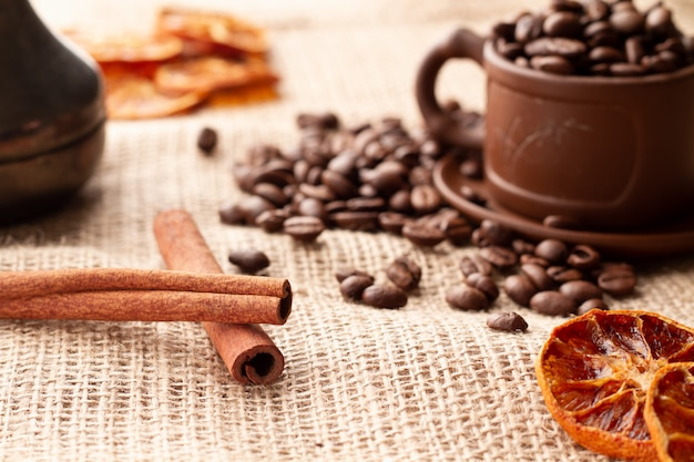 Two sticks of natural cinnamon next to the coffee beans