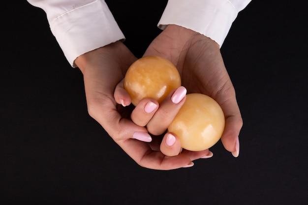 女性の手に2つの石のボール