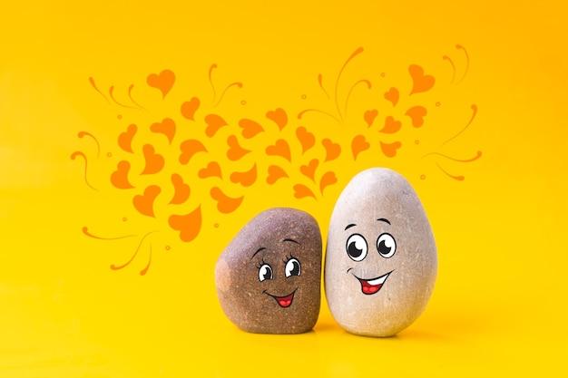 黄色の背景に互いに恋をしている変な顔が描かれた2つの石。愛、バレンタインデーのコンセプト。混血のカップル。