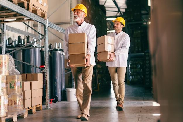 重い箱を運ぶ作業服の2人の倉庫作業員。