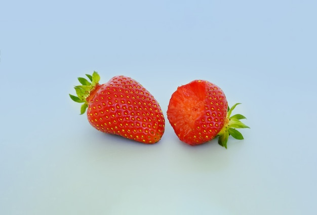 Two strawberries with strawberry leaves on a gray background. whole and bitten berries.
