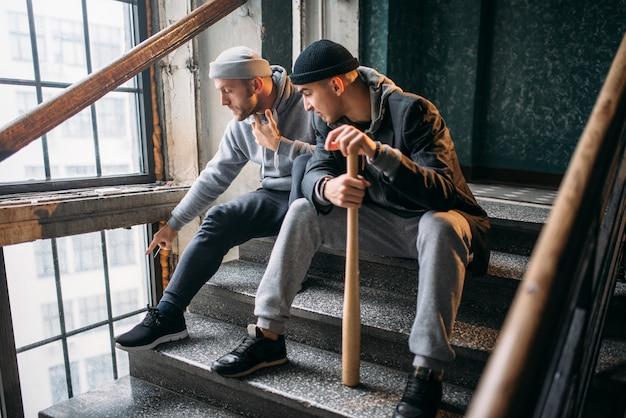 Два уличных бандита с бейсбольной битой ждут жертву. криминал, опасность ограбления, опасные парни