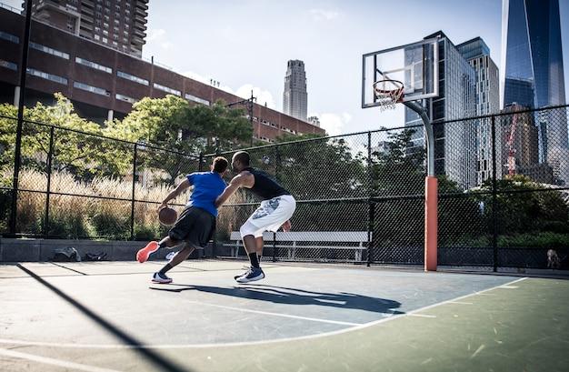 법원에서 열심히 놀고있는 두 길거리 농구 선수
