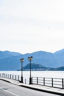 Два уличных фонаря на берегу озера комо в италии с видом на горы.