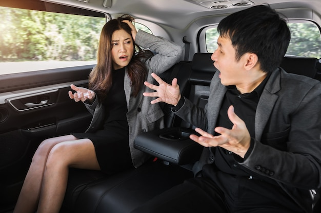 차 뒷좌석에 앉아 말다툼을 하는 두 명의 스트레스 받는 사업가와 여성