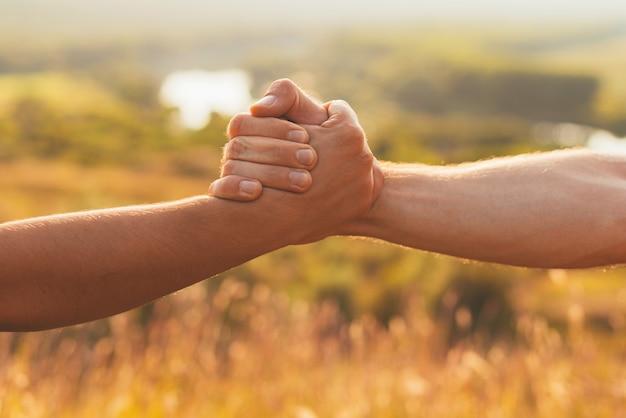두 개의 강한 손이 도움과 협력을 위해 서로 잡고 있습니다.