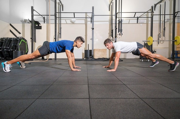 Two strong men doing pushups in gym