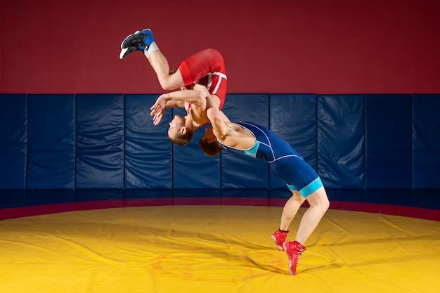 青と赤のレスリングタイツの2人の強いレスラーが、ジムの黄色のレスリングカーペットに腰を投げています。