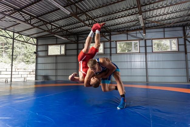 Два сильных борца в синем и красном трико борются на борцовском ковре в тренажерном зале.