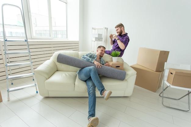 Два студента-друга-мужчины держат свои вещи в руках, сидя в гостиной новой квартиры. концепция новоселья.