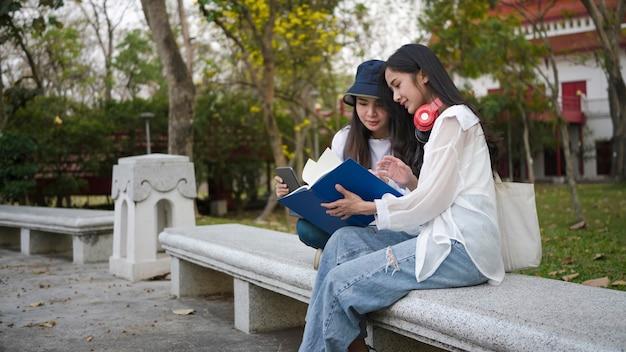 Два студента сидят и читают книгу в парке на территории кампуса.