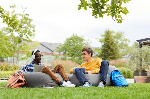 Два студента отдыхают на природе в кампусе