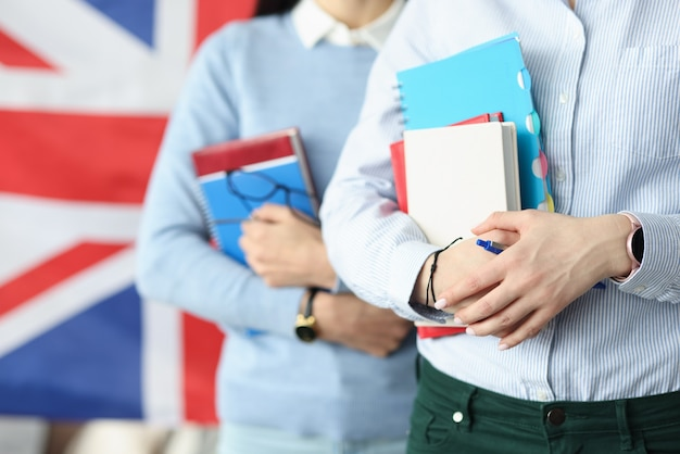 Two students hold notebooks against background of flag of england. learning english concept