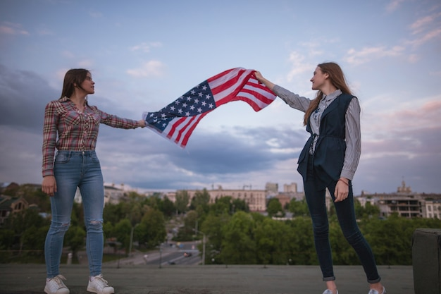 Two students holds flying american flag. happy girls on roof. teenager sisters on vacation celebrate the independence day
