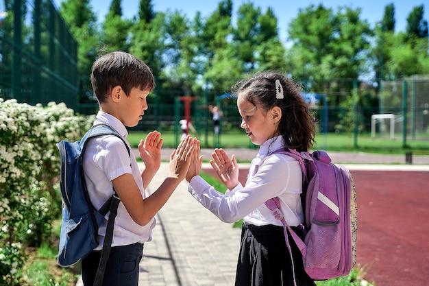 Двое учеников в белой рубашке с ранцами играют во дворе школы