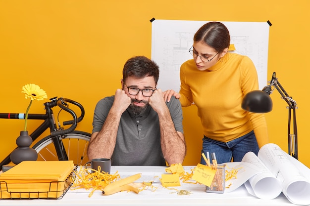 Two students prepare for upcoming examination sit at office desk with papers blueprints and sketches. frustrated unhappy bearded man feels tired after preparing architectural project. teamworking