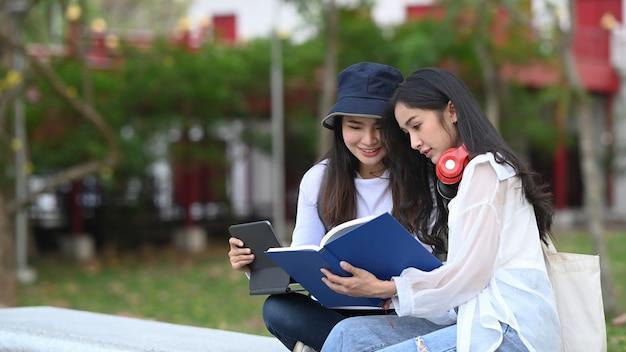 Два студента читают книгу и разговаривают друг с другом в кампусе.