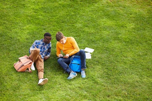 Двое студентов отдыхают на зеленой траве