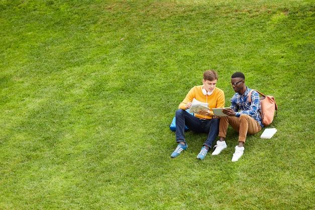 草の上で休んでいる2人の学生